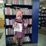Dziewczynka z książką i kartą biblioteczną stoi na tle regałów z ksiązkami