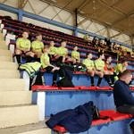 Widok na trybuny - w żółtych koszulkach siedzi drużyna LKS Wola Krzysztoporsk