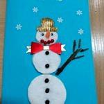 Ręcznie robiona kartka świąteczna - bałwanek z płatków kosmetycznych na niebieskim tle