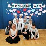 Grupa dzieci w strojach galowych siedzi na scenie; z tyłu na niebieskim tlw napis Kochamy Was i serduszka