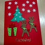 Ręcznie robiona kartka świąteczna - jelonki, choinka i prezent na czerwonym tle