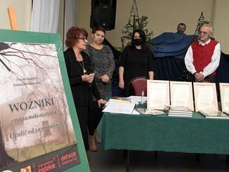 Spotkanie promocyjne w Woźnikach - Za stołem z egzemplarzami ksiązki stoją autorki i przedstawiciele Fundacji Wspierania Folkloru Wiejskiego i Miejskiego w Mzurkach; obok stojak z okładkąksiążki