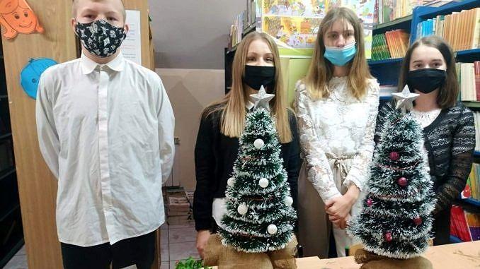 Grupa uczniów prezentuje wykonane własnoręcznie choinki