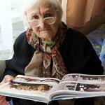 Starsza pani (Zofia Szymańska) ogląda stare fotografie w wydanej książce