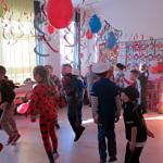 Grupa dzieci w przebierańcowych strojach bawi się na sali udekorowanej balonami i serpentyną