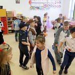Grupa dzieci w przebierańcowych strojach bawi się na sali