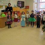 Grupa dzieci w przebierańcowych strojach razem z opiekunką
