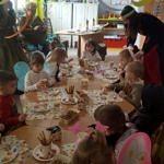 Grupa przedszkolaków w kolorowych przebraniach - przy stole podczas jedzenia przekąsek