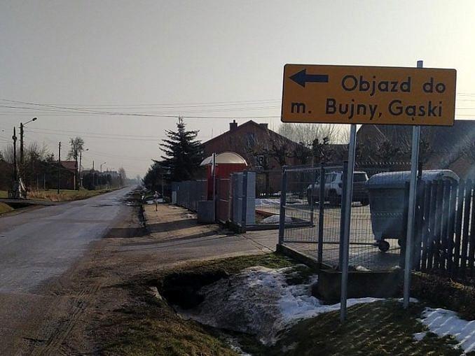 Droga i żółty znak objazdu z napisem: objazd m. Bujny, Gąski