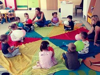 Dzieci z opiekunkami siedzą w kręgu na kolorowej tęczowej macie i podają sobie balonik