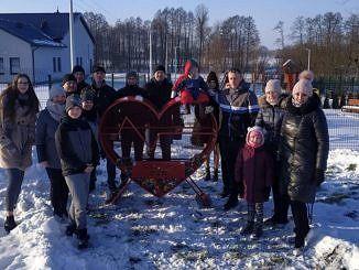 Grupa ludzi stoi przy metalowym, czerwonym sercu - pojemniku na plastikowe nakrętki
