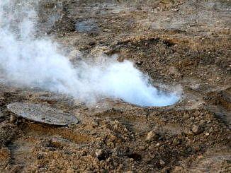 Dym unoszący się znad studzienki kanalizacyjnej