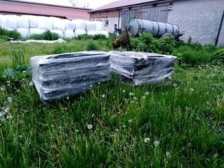Azbest - tzw. eternit owinięty folią, składowany na paletach, na trawie