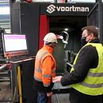 Dwaj mężczyźni w kamizelkach odblaskowych oglądają maszynę produkcyjną