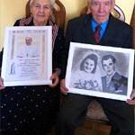 Dwoje starszych ludzi siedzi z obrazami w rękach; pani trzyma obrazek z gratulacjami od papieża Franciszka, pan trzyma ich portret ślubny z młodości