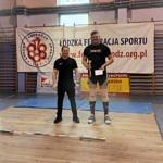 Trener i zawodnik stoją na tle baneru Łodzkiej Federacji Sportu