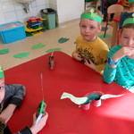 Dzieci pdczas zabaw przy stole; Dzieci z wykonanymi własnoręcznie dinozaurami