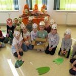 Grupa dzieci przedszkolnych w dinozaurowych maskach