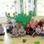 Grupa dzieci siedzi na tle dużego, zielonego dinozaura