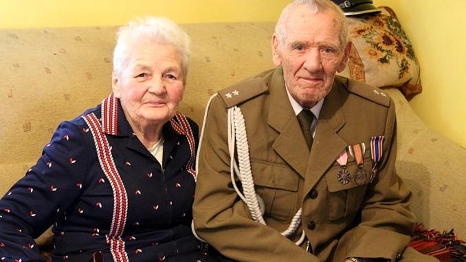 Dwoje starszych ludzi siedzi na wersalce - pani Zofia w granatowej sukience w czerwone paski; obok pan Zdzisław w mundurze wojskowym