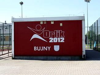 zdjęcie bordowego kontenera dla administratora orlika z białym napisem Orlik 2012 Bujny