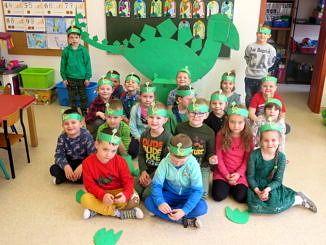 Grupa dzieci przedszkolnych siedzi na podłodze z zielonymi opaskami z dinozaurami na głowach