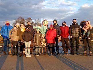 kolkanaście osób w maseczkach stoi na moście nad rzeką, gdzie topili marzannę