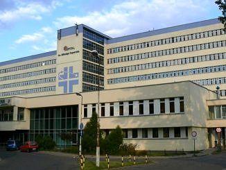 Front szpitala im. Kpernika w Łodzi; szary, duży budynek; nad wejściem logo w postaci niebieskiego podwójnego krzyża
