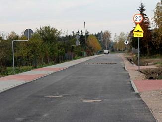 Asfaltowa ulica z chodnikiem z kostki brukowej