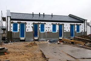 Budynek komunalny z brązowym dachem w trakcie budowy; otwory drzwiowe i okienne przysłonięte niebieską folią