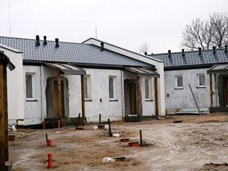 Budynki komunalne w budowie - białe budynki pokryte dachem; ganek podparty drewnianymi belkami