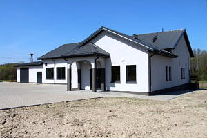 Dom Ludowy w Blizinie; biały budynek z brązowym, spadzistym dachem; przes nim mały przedsionek