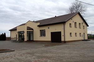 dom ludowy w Oprzężowie - jasny budynek z brązowym dachem i oszklonym gankiem
