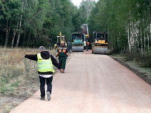 Prace drogowe; walce utwardzają nawierzchnię; człowiek w odblaskowej kamizelce wskazuje ręką na pobocze