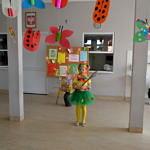 Dziewczynka w kolorowym wiosennym stroju - żółta bluzka i rajstopy, zielona spódniczka wianek na głowie