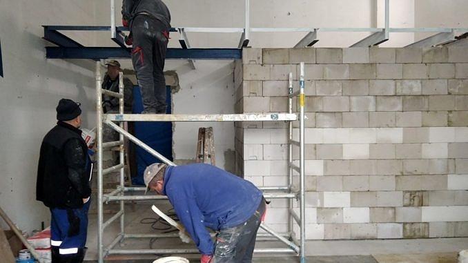 Wnętrze pomieszczenia, ścianka z pustaków, a przy niej rusztowanie i czterej pracownicy