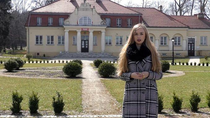 Młoda kobieta stoi na tle dworku - Szkoły Podstawowej w Parzniewicach