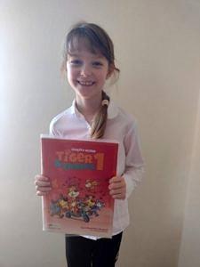 Joanna - usmiechnięta dziewczynka z czerwoną książką od angielskiego