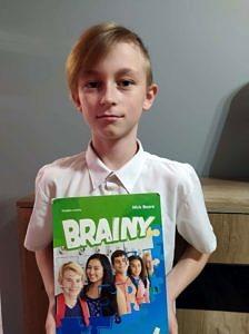 Julian - jasnowłosy chłopiec w bialej koszuli z książką od angielskiego