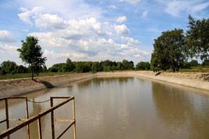 Zbiornik retencyjny w Wol Krzysztoporskiej; tafla wody, błękitne niebo z białymi chmurami