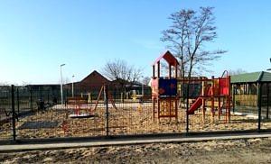 Plac zabaw i siłownia zewnętrzna w Krzyżanowie; kolorowe urządzenia na pogrodzonym placu