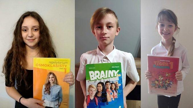 Troje laureatów konkursów - Nicole - długowłosa dziewczynka z żółta książką od angielskiego, Julian - jasnowłosy chłopiec w bialej koszuli z książką od angielskiego, Joanna - usmiechnięta dziewczynka z czerwoną książką od angielskiego