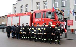 Na tle budynku Urzedu Gminy stoi nowy czerwony samochód strażacki, a przed nim grupa ludzi - w tym strażacy, wójt i przedstawiciele urzędu gminy