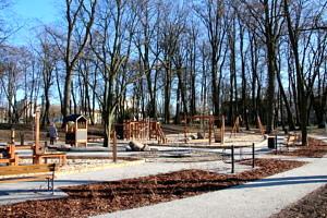 Park w Woli Krzysztoporskiej; drzewa bez liści, plac zabaw z drewnianymi urządzeniami; alejki parkowe