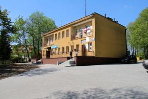 Żółty piętrowy budynek ze schodami i podestem, a przed nim utwardzony kostką plc - prking