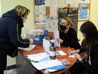 kobieta w maseczce przy biurku składa wniosek; odbieraja go dwie urzedniczki w maseczkach; oddziela je przezroczysta osłona; na biurku płyn do dezynfekcji