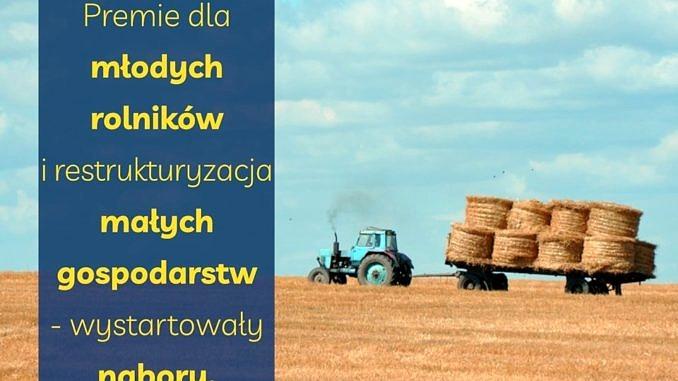 plakat po lewej stronie żółty napis na niebieskim tle premie dla młodych rolników; po prawej stronie pole, ściernisko a na nim ciągmik przewożocy bele słomy; w tle błękitne niebo