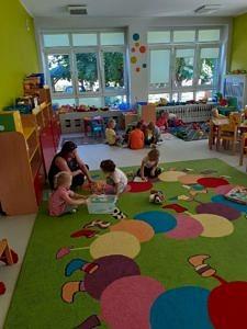 Kolorowa sala przedszkolna z nowymi podłogami i kolorowym dywanem, na którym bawią się dzieci
