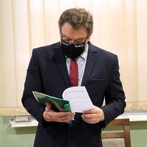 Wójt Roman Drozdek stoi w czarnej maseczce; w rękach trzyma rozłożony plik dokumentów