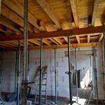 Remontowane pomieszczenie - drewniane belki i strop podparte belkami